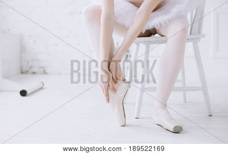 Young ballerina in white tutu sitting on the stool and holding her right foot with both hands. Maybe she hurt it while she was stretching or dancing