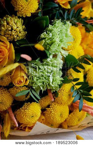 Yellow bouquet with green carnation, in the composition of chrysanthemums, roses and dyed grains