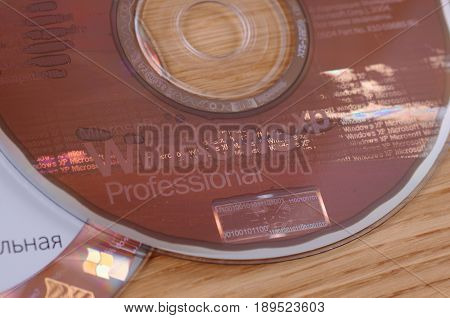 SARANSK, RUSSIA - MAY 24, 2017: Windows XP CD disk on wooden background.