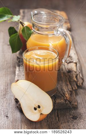 Pear juice in a glass beaker and jug fresh pears on an old wooden background
