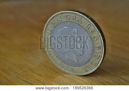 Macro detail of a silver and golden coin with head of queen in a value of two British Pounds (2 GBP) on the wooden surface as a symbol of currency used in the United Kingdom of Great Britain