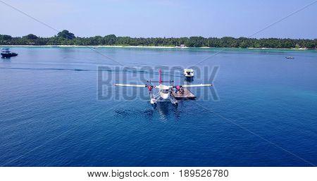Aerial flying drone view of Maldives white sandy beach airplane seaplane sunny tropical paradise island with aqua blue sky sea ocean 4k