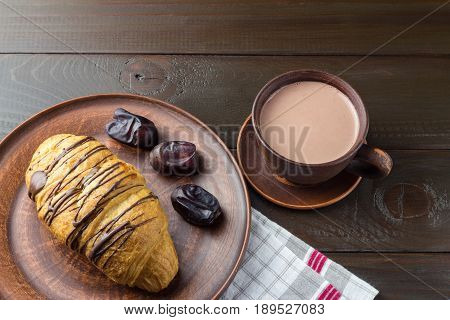 Hot chocolate or cocoa drink in cup and sweet croissant and dates fruit at plate on napkin dark brown wooden table.