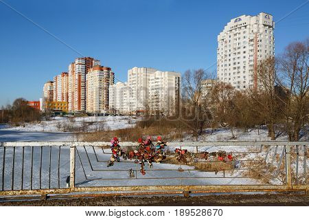 Love locks on the bridge against the background of a new residential district. Balashikha, Moscow region, Russia.