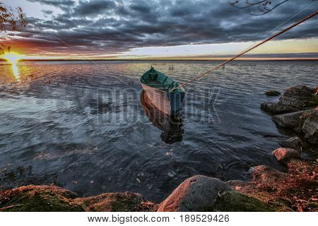 the attached wooden boat has pulled a rope as a string and aspires in swimming at sunset