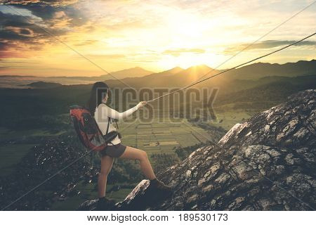 Image of Asian female hiker holding a rope while climbing a steep mountain. shot at sunrise time