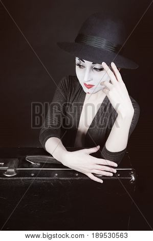 The woman mime sits next to the suitcase waiting for the trip. Theatrical Performance