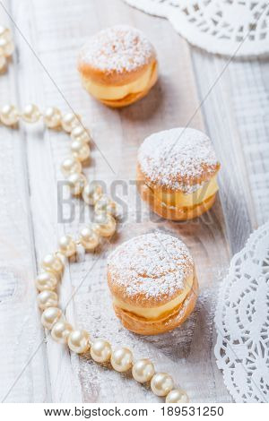 Profiterole or cream puff cakes filled with whipped cream on wooden background close up. Delicious dessert with decor. Top view