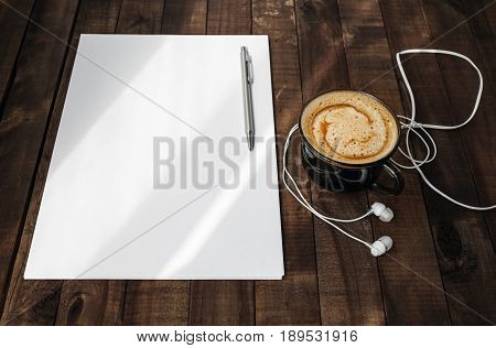 Photo of blank stationery on vintage wooden table background. Blank letterhead coffee cup headphones and pen. Blank branding template. Mock up for placing your design. Top view.