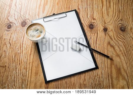 Clipboard with a blank letterhead pencil and sharpener on wood table background. Blank template with plenty of copy space. Responsive design mockup. Top view.