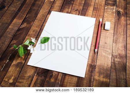 Blank stationery: letterhead pencil eraser and cherry flowers and green leaves on wooden table background. Mock up for placing your design.