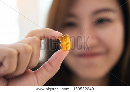 Closeup image of a beautiful Asian woman smiling holding and looking at orange gummy bear