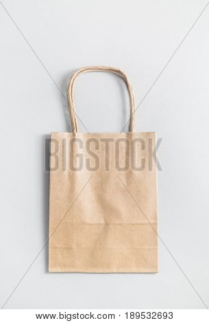 Recycled craft paper shopping bag on paper background. Vertical shot.