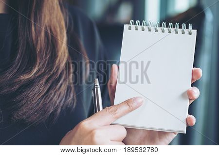 Closeup image of a woman holding notebook in office