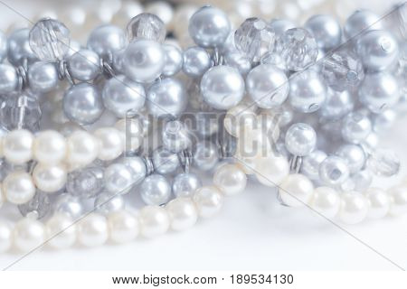 Abstract blurred background pearl silver necklace on white. Macro shot Shallow depth of field defocused