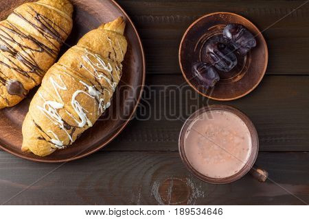 Hot chocolate or cocoa drink in cup and sweet croissants and dates fruit at plate on dark brown wooden table top view.