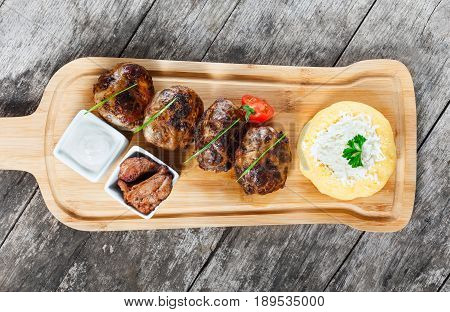 Juicy delicious meat cutlets and hominy Corn porridge Polenta with goat cheese on cutting board on wooden background . Hot Meat Dishes. Top view
