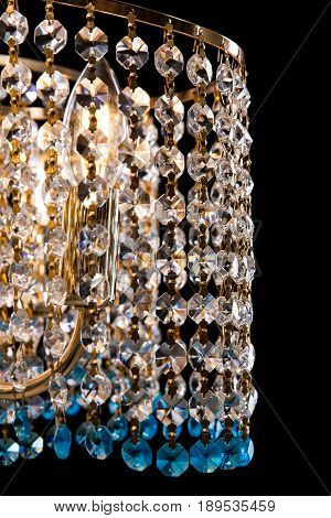 Large crystal chandelier details decorated transparent and blue crystals isolated on black background. Luxury royal expensive chandelier for living room, Hall of celebration.