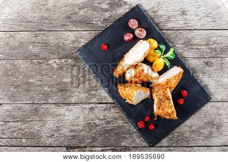 Grilled chicken breasts with vegetables and berries on stone slate background on wooden background close up. Hot Meat Dishes. Top view