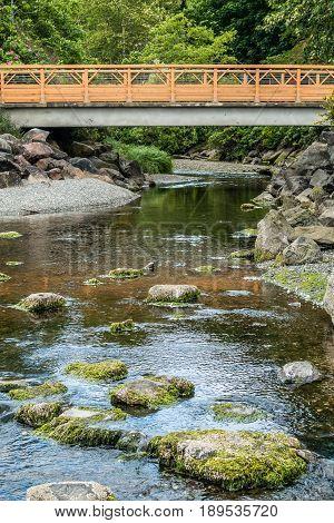 A walking bridge spans a stream in Des Moines Washington.