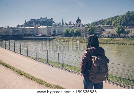 Austria. Salzburg. Girl Tourist Standing On The Banks Of The Salzach River And Looking At The Old To