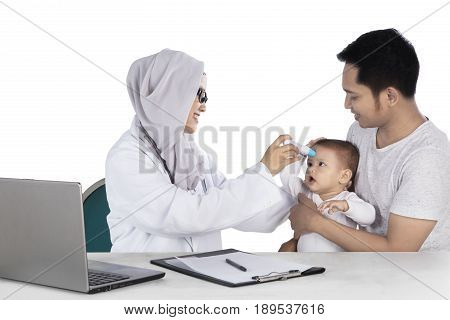 Muslim pediatrician using a digital thermometer to check the baby temperature with laptop on the table