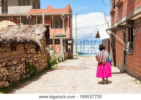 Island of Sun (Isla del Sol) Titicaca lake Bolivia - March 23 2017. Local woman in national clothing walking down the street of a small town