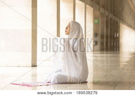Muslim woman wearing prayer veil praying for Allah muslim god
