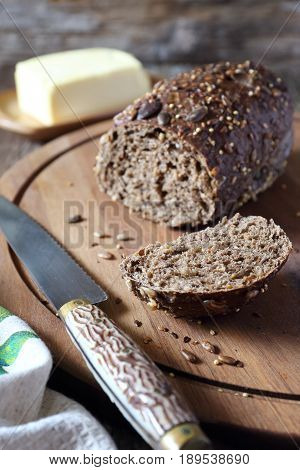 Rye french bread and butter on wooden chopping board