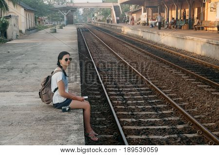 Sri Lanka. Hikkaduwa. Girl tourist with a ticket in her hands crouched on the edge of the platform in anticipation of the train