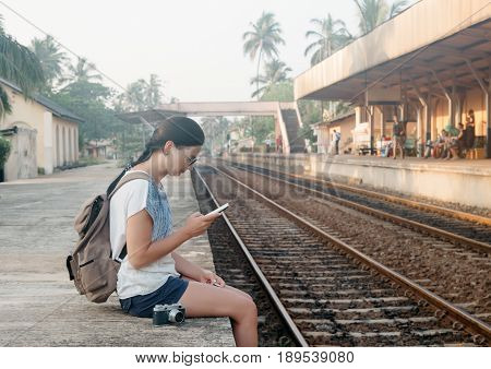 Sri Lanka. Hikkaduwa. Girl tourist with the phone in her hands crouched on the edge of the platform in anticipation of the train