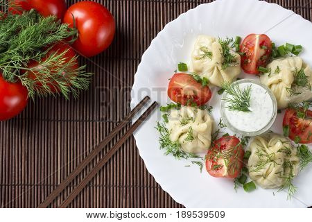 Manty with meat greens and tomatoes on a wooden background Tatar Uzbek Kyrgyz Kazakh Bashkir Crimean Chinese dumplings with meat