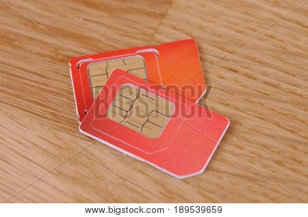 Pair SIM card (Sibscriber Identity Module) on a wooden table.