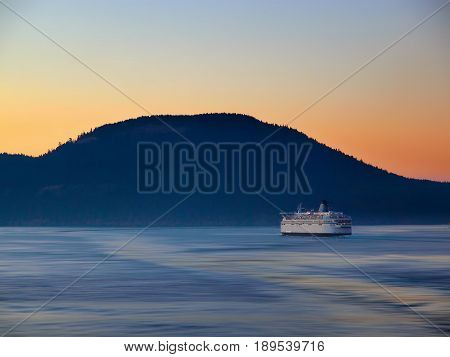 Ferry making its way by the island at the sunset time