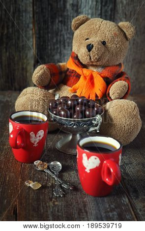 Teddy bear two cups of coffee and chocolate drops. Toned image