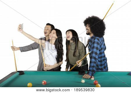 Group of happy multiracial people taking a selfie photo together next to pool table isolated on white background