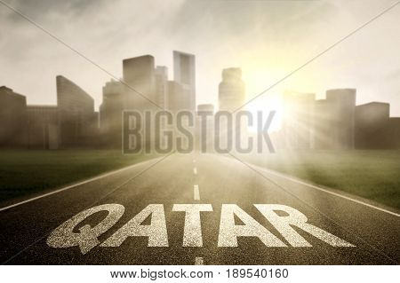 Image of asphalt road towards to a town and sunrise with Qatar word