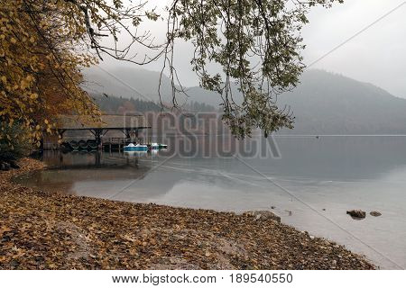 Hohenschwangau near Fussen in Bavaria Germany. Boat station on the Alpsee lake surrounded by autumn forest.