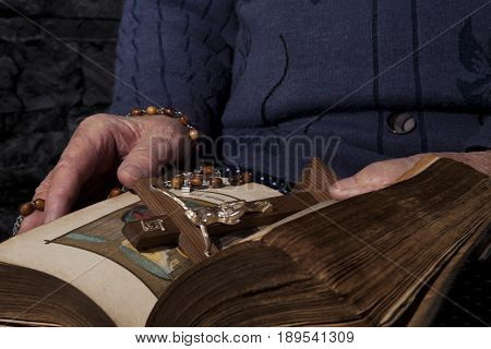 Grandma with rosary and cross reading bible. Faith and religion.