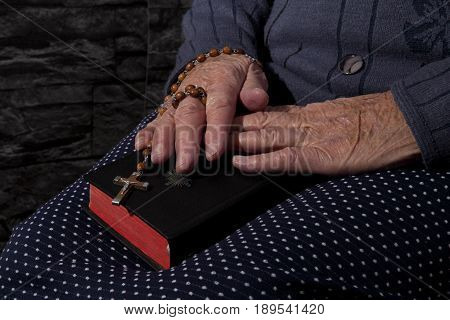Grandma with rosary and bible praying. Faith and religion.