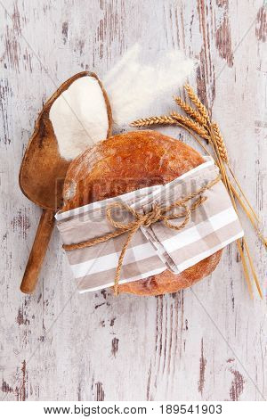 Bread with flour on wooden table top view. Bakery concept.