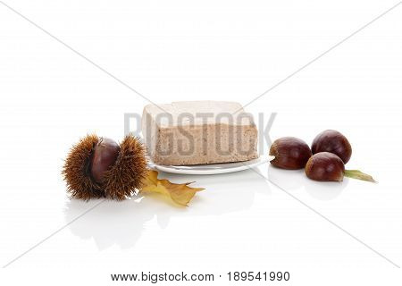 Chestnut puree with raw chestnuts isolated on white background.
