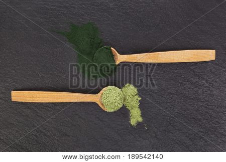 Chlorella and barley grass powder on wooden spoon on black background top view. Detox and superfood concept.
