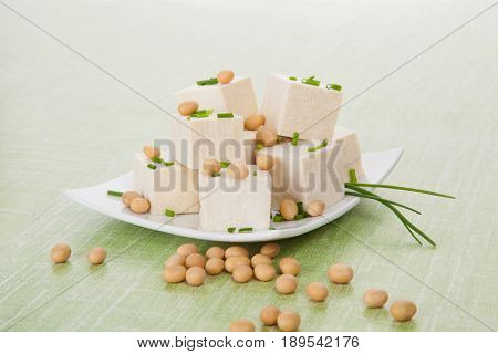 Tofu and soybeans on green background. Natural vegan and vegetarian eating.