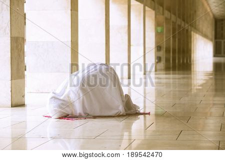 Muslim woman wearing prayer veil doing prostration in the mosque