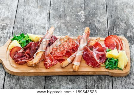 Antipasto platter cold meat plate with grissini bread sticks prosciutto slices ham beef jerky salami and arugula on cutting board on wooden background. Meat appetizer. Top view