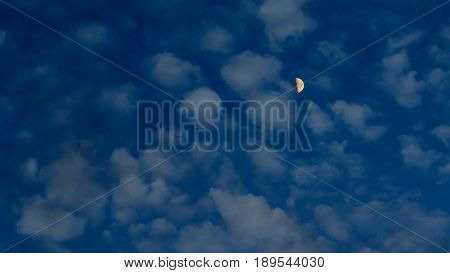 Yellow half moon in the clouds at dusk