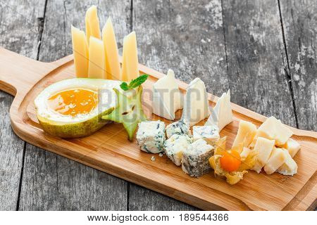 Cheese platter garnished with pear honey carambola physalis on cutting board on wooden background. Snacks and Wine appetizers set. Top view