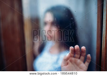 Young melancholy and sad girl portrait behind the window in the rain with rain drops on window. Hand touches the window. Conception is the romance of youth, blues and blahs