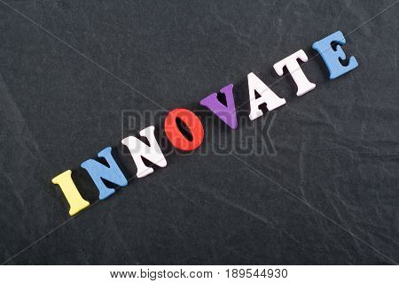 INNOVATE word on black board background composed from colorful abc alphabet block wooden letters, copy space for ad text. Learning english concept
